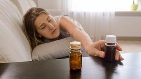 Φωτογραφία κινηματογραφήσεων σε πρώτο πλάνο της νέας γυναίκας που φθάνει για τα φάρμακα στον πίνακα πλευρών Στοκ Εικόνες