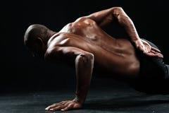 Φωτογραφία κινηματογραφήσεων σε πρώτο πλάνο του αμερικανικού αρσενικού αθλητή afro που κάνει το ένας-PU Στοκ Εικόνες