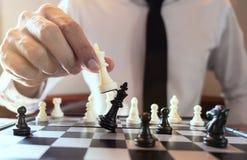 Φωτογραφία κινηματογραφήσεων σε πρώτο πλάνο του σκακιού παιχνιδιού επιχειρηματιών και του κτυπώντας μαύρου σογιού στοκ εικόνες