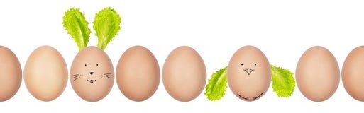 Φωτογραφία κινηματογραφήσεων σε πρώτο πλάνο των αυγών hen's με eggshell τη σύσταση σε μια σειρά Αστεία λαγουδάκι και κοτόπουλο  στοκ εικόνες