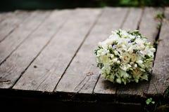 Φωτογραφία κινηματογραφήσεων σε πρώτο πλάνο των γαμήλιων δαχτυλιδιών και της γαμήλιας ανθοδέσμης που βάζουν στο θόριο Στοκ Εικόνες