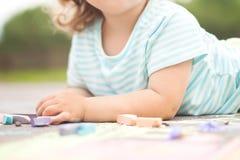 Φωτογραφία κινηματογραφήσεων σε πρώτο πλάνο, σχέδιο κοριτσιών μικρών παιδιών με το κομμάτι της κιμωλίας χρώματος Στοκ εικόνες με δικαίωμα ελεύθερης χρήσης