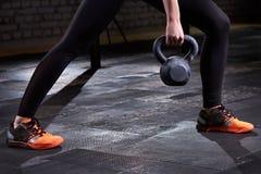 Φωτογραφία κινηματογραφήσεων σε πρώτο πλάνο των νέων ποδιών γυναικών ` s στις περικνημίδες και τα sneackers και kettlebell στο σκ Στοκ φωτογραφίες με δικαίωμα ελεύθερης χρήσης