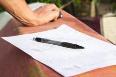 Φωτογραφία κινηματογραφήσεων σε πρώτο πλάνο των χεριών σχεδίων και του ξυλουργού που πρόκειται να κάνουν το σχέδιο Στοκ φωτογραφία με δικαίωμα ελεύθερης χρήσης