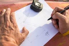 Φωτογραφία κινηματογραφήσεων σε πρώτο πλάνο των χεριών σχεδίων και του ξυλουργού που πρόκειται να κάνουν το σχέδιο Στοκ Εικόνες