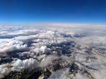 Φωτογραφία μεγάλου υψομέτρου των χιονισμένων ορών με το μπλε ουρανό και τα άσπρα σύννεφα που καλύπτουν τη γη με τον κυρτό ορίζοντ Στοκ Εικόνες