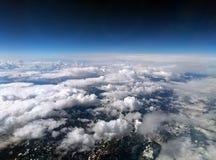 Φωτογραφία μεγάλου υψομέτρου των χιονισμένων ορών με το σκοτεινό ουρανό και τα άσπρα σύννεφα που καλύπτουν τη γη με τον κυρτό ορί Στοκ Φωτογραφίες