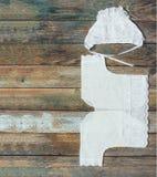 Φωτογραφία μιας ΚΑΠ και ενός πουκάμισου για έναν νεογέννητο σε μια παλαιά αγροτική ξύλινη επιτραπέζια κινηματογράφηση σε πρώτο πλ Στοκ Εικόνες