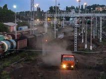 φωτογραφία νύχτας γραμμών χρωμάτων Κατασκευή στο σιδηρόδρομο φορτηγό που συναγωνίζεται κάτω από το δρόμο που κλωτσά επάνω τη σκόν στοκ φωτογραφία με δικαίωμα ελεύθερης χρήσης