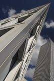 Φωτογραφία τέχνης ενός ουρανοξύστη: η οξεία γωνία των ανόδων κτηρίου στο μπλε ουρανό, οι ενάρξεις των παραθύρων, το τεμάχιο του τ Στοκ Φωτογραφία