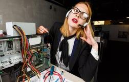 Φωτογραφία της γυναίκας με τα γυαλιά και τα ακουστικά στον πίνακα δίπλα στο σπασμένο επεξεργαστή στοκ φωτογραφία με δικαίωμα ελεύθερης χρήσης