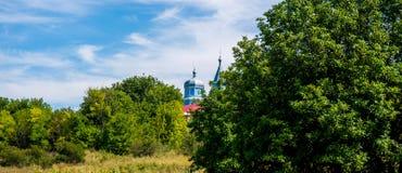 Φωτογραφία της μπλε εκκλησίας μεταξύ των πράσινων δέντρων Στοκ Εικόνα