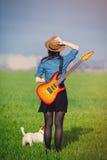 Φωτογραφία της νέας γυναίκας με την κιθάρα και του σκυλιού Στοκ Εικόνα
