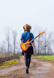 Φωτογραφία της νέας γυναίκας με την κιθάρα Στοκ Φωτογραφία