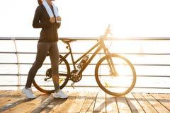 Φωτογραφία της χαλαρωμένης γυναίκας με την πετσέτα πέρα από το λαιμό που στέκεται κοντά στο ποδήλατο υπαίθρια, μετά από το workou στοκ φωτογραφίες
