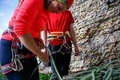 Φωτογραφία του άνδρα και της γυναίκας στην κόκκινη μπλούζα με το σχοινί ασφάλειας στο υπόβαθρο του βουνού στοκ εικόνες