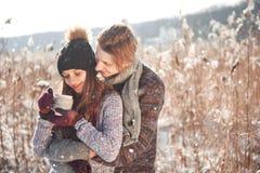 Φωτογραφία του ευτυχούς άνδρα και της όμορφης γυναίκας με τα φλυτζάνια υπαίθρια το χειμώνα Χειμερινές διακοπές και διακοπές Ζεύγο στοκ εικόνες