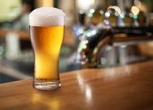 Φωτογραφία του κρύου γυαλιού μπύρας σε έναν φραγμό.
