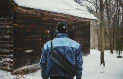 Φωτογραφία του οδοιπόρου τυχοδιωκτών στο χιονισμένο δάσος μπροστά από την εγκαταλειμμένη άποψη εξοχικών σπιτιών από την πλάτη του στοκ φωτογραφία με δικαίωμα ελεύθερης χρήσης
