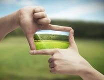 Φωτογραφία του πράσινου πεδίου στα χέρια Στοκ εικόνα με δικαίωμα ελεύθερης χρήσης