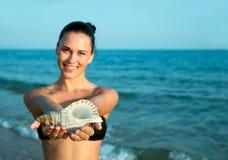 Φωτογραφία του όμορφου προτύπου με το μεγάλο θαλασσινό κοχύλι στα χέρια relaxin Στοκ Εικόνες