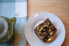 Φωτογραφία τροφίμων και ποτών ενός σπιτικού κέικ με τα καρύδια και των φρούτων με teapot γυαλιού του καυτού πράσινου τσαγιού με τ Στοκ εικόνα με δικαίωμα ελεύθερης χρήσης