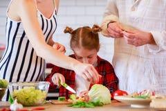 Φωτογραφία των γονέων με τα μαγειρεύοντας τρόφιμα κορών στην κουζίνα Στοκ εικόνες με δικαίωμα ελεύθερης χρήσης