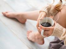 Φωτογραφία των θηλυκών ποδιών και των χεριών που χαλαρώνουν και που πίνουν τον καφέ στο κρεβάτι Στοκ Φωτογραφία