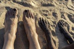 Φωτογραφία των ποδιών του νέου καυκάσιου κοριτσιού και του ποδιού του σκυλιού στην άμμο στη θερινή παραλία Πόδια Selfi στοκ φωτογραφίες