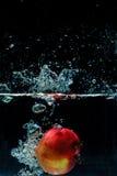 Φωτογραφία υψηλής ταχύτητας του μήλου με τον παφλασμό στο νερό Στοκ Εικόνες