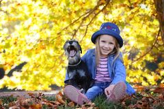 Φωτογραφία φθινοπώρου τρόπου ζωής, μικρό κορίτσι και μικροσκοπικό σκυλί schnauzer που περπατούν υπαίθρια στοκ φωτογραφία