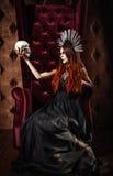 Φωτογραφία φρίκης: το όμορφο κορίτσι goth στο μαύρο φόρεμα κρατά το κρανίο Στοκ φωτογραφία με δικαίωμα ελεύθερης χρήσης