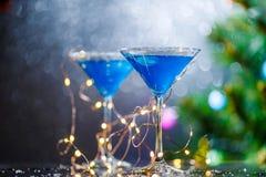 Φωτογραφία Χριστουγέννων δύο γυαλιών κρασιού με το μπλε κοκτέιλ και τη γιρλάντα Στοκ φωτογραφία με δικαίωμα ελεύθερης χρήσης