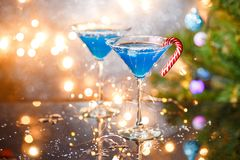 Φωτογραφία Χριστουγέννων δύο γυαλιών κρασιού με το μπλε κοκτέιλ και τη γιρλάντα Στοκ Εικόνες