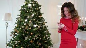 Φωτογραφία χριστουγεννιάτικων δέντρων, κορίτσι που φωτογραφίζεται σε ένα κινητό τηλεφωνικό χριστουγεννιάτικο δέντρο με τα παιχνίδ απόθεμα βίντεο