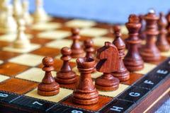 Φωτογραφία χρώματος του πίνακα σκακιού και των κομματιών σκακιού, ξύλινα κομμάτια σκακιού στη σκακιέρα Κοράκι στο πρώτο πλάνο στρ Στοκ Φωτογραφία