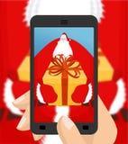 Φωτογραφία Santa Χριστουγέννων για να δώσει το δώρο Φωτογράφιση του smartphon σας απεικόνιση αποθεμάτων