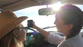 Φωτογραφία Selfi στο smartphone των φίλων πίσω από το αυτοκίνητο ροδών, κορίτσια που φωτογραφίζονται στη συσκευή στο μπροστινό κά απόθεμα βίντεο