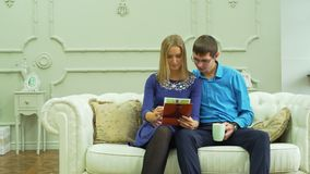 Φωτογραφίες εξέτασης ζεύγους και τσάι κατανάλωσης σε έναν καναπέ απόθεμα βίντεο