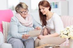 Φωτογραφίες προσοχής Caregiver επισκεμμένος την ευτυχή ηλικιωμένη γυναίκα στο σπίτι στοκ εικόνα