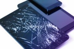 Φωτογραφίες της ραγισμένης επίδειξης σε μια ταμπλέτα και ένα μαύρο κινητό τηλέφωνο που απομονώνονται στο λευκό Ταμπλέτα με τη χαλ στοκ εικόνα με δικαίωμα ελεύθερης χρήσης