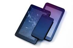 Φωτογραφίες της ραγισμένης επίδειξης σε μια ταμπλέτα και ένα μαύρο κινητό τηλέφωνο που απομονώνονται στο λευκό Ταμπλέτα με τη χαλ στοκ εικόνες