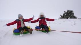 Φωτογραφικές διαφάνειες παιδιών στο χιόνι σε ετοιμότητα έναν διογκώσιμοι σωλήνα χιονιού και κυμάτων Ευτυχείς φωτογραφικές διαφάνε φιλμ μικρού μήκους
