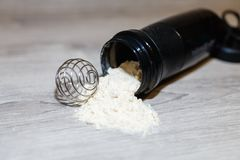 Φωτογραφική διαφάνεια από την πρωτεΐνη ορρού γάλακτος, καζεΐνη ή αποβουτυρωμένο γάλα, άνοιξη για το μίγμα κοντά σε έναν μαύρο δον στοκ εικόνα