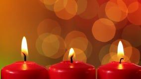 Φωτογραφική διαφάνεια μπροστά από το κάψιμο των κεριών Χριστουγέννων ενάντια στα μουτζουρωμένα φω'τα Χριστουγέννων απόθεμα βίντεο
