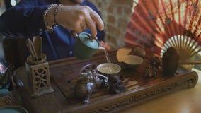 Φωτογραφική διαφάνεια που βλασταίνεται του ατόμου που χύνει το πράσινο τσάι από teapot σε gaiwan στην τελετή τσαγιού παραδοσιακού απόθεμα βίντεο