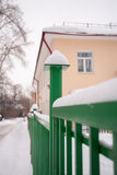 Φωτογραφική διαφάνεια χιονιού στον πράσινο φράκτη στο υπόβαθρο σπιτιών στοκ φωτογραφία με δικαίωμα ελεύθερης χρήσης