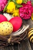 Φωλιά αυγών Πάσχας με τα λουλούδια στο αγροτικό ξύλινο υπόβαθρο στοκ εικόνα με δικαίωμα ελεύθερης χρήσης