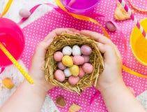 Φωλιά Πάσχας εκμετάλλευσης παιδιών με τα αυγά καραμελών σοκολάτας, Πάσχα συμπυκνωμένο Στοκ Φωτογραφία