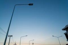 Φω'τα λαμπτήρων οδών νύχτας με το υπόβαθρο ηλιοβασιλέματος Στοκ εικόνες με δικαίωμα ελεύθερης χρήσης